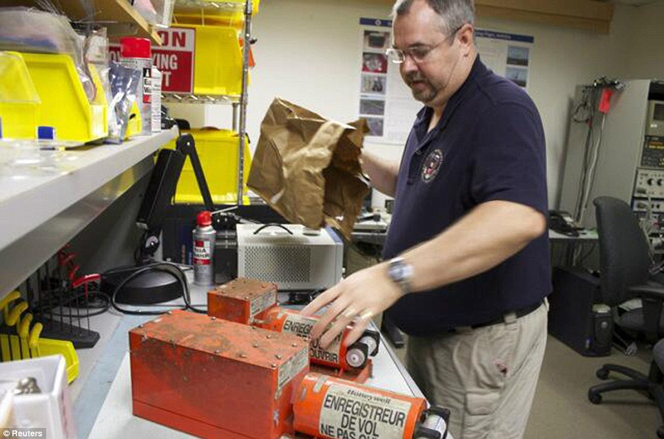 Black box: Greg Smith of the National Safety Board collects the flight data recorder and cockpit voice recorder from Flight 214