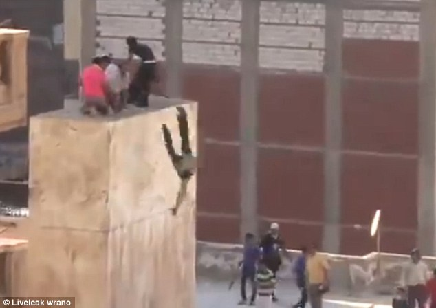 Victim: The first teenager falls off the ledge and lies motionless as the mob gathers around his body