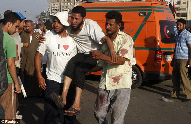 Injured: Supporters of deposed Egyptian president Mohamed Morsi help a wounded protester outside the Republican Guard headquarters in Cairo