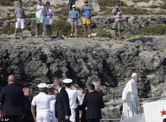 Pope Francis, right, boards an Italian Coast Guard boat upon his arrival. This first official trip outside Rome is highly symbolic for the new pontiff, who has placed the poor and dispossessed at the centre of his papacy