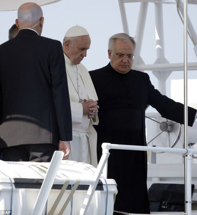 Pope Francis prays after throwing a wreath of flowers into the sea in memory of migrants who never arrived to Lampedusa