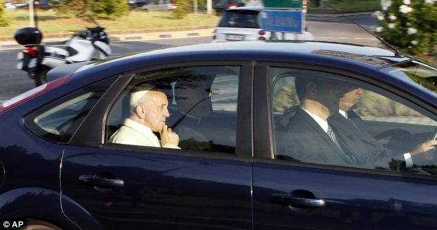 Pope Francis is seen inside his car after he urged other priests to not drive flashy cars as it 'pains him' to see them spending so much money