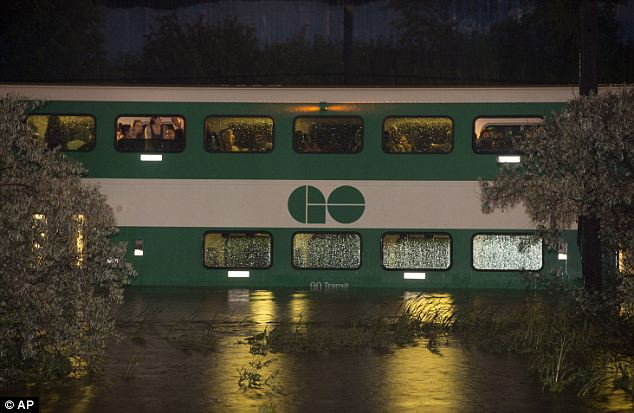Up above: Commuters were forced to the upper decks by the water rising below