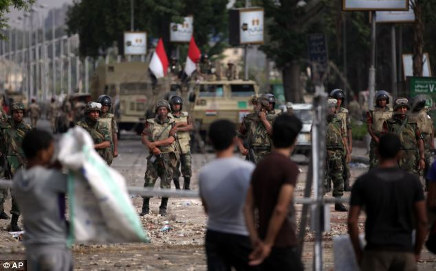 Tension: Supporters of ousted President Mohamed Morsi protest as army soldiers guard at the Republican Guard building today