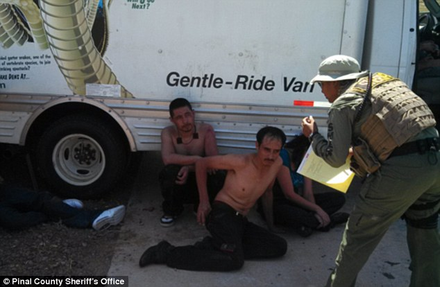 Exhaustion: Three of the immigrants are pictured slumped next to the U-Haul van after being discovered by local sheriffs