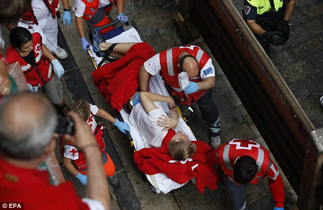 Emergency: Red Cross personnel carry a runner on a stretcher to receive treatment after being gored