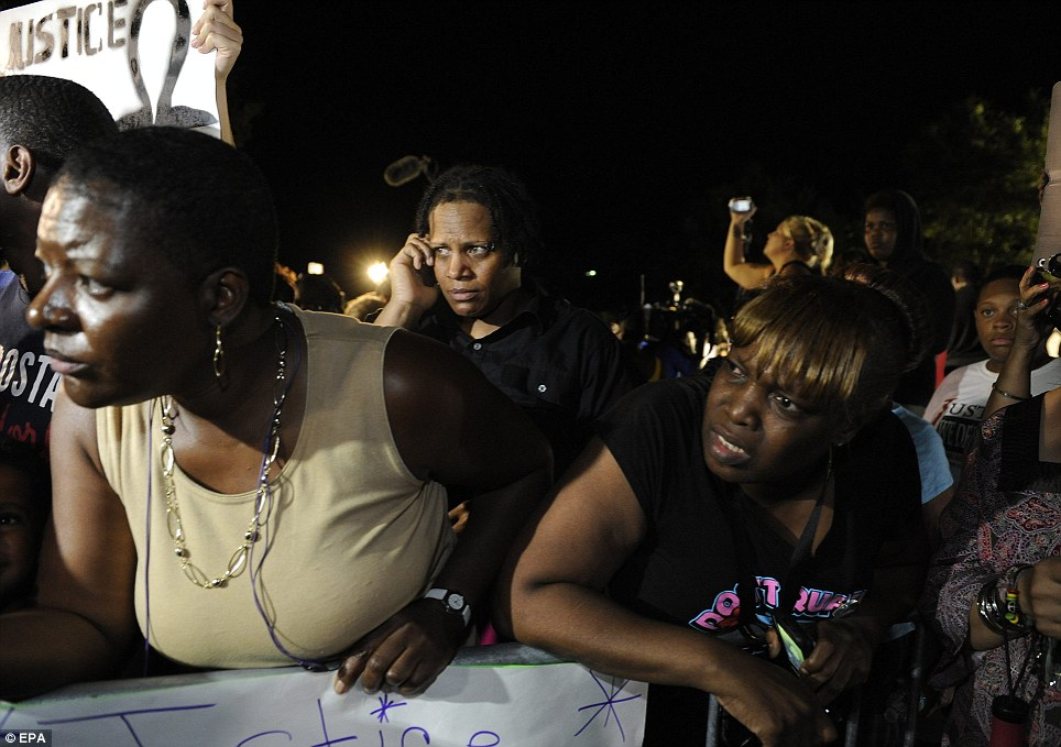 Demonstrators stare in disbelief after they hear the news the George Zimmerman is found not guilty by the all female jury