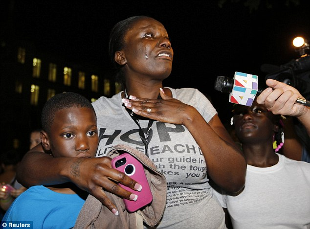 Darssie Jackson (C) reacts with her children Linzey Stafford, 10, (L) and Shauntiana Stafford outside Seminole County Court where George Zimmerman was found not guilty on second-degree murder and manslaughter charges