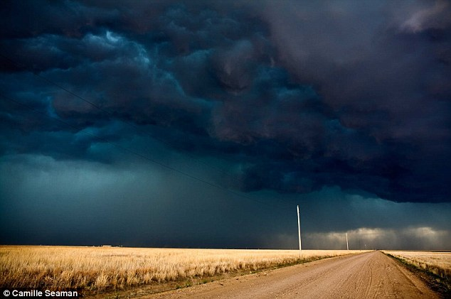Bruised: Clouds look like they have been stained with blue and purple ink as a storm forms over this dusty road