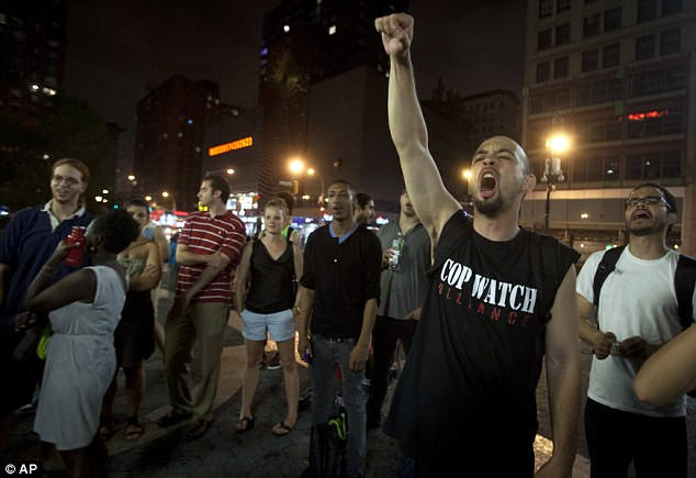 Outrage: A man screams during a demonstration in downtown Manhattan after the news that George Zimmerman was found not guilty in the 2012 shooting death of Martin