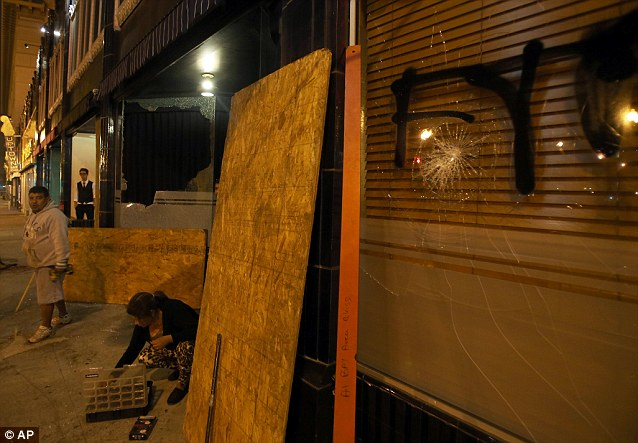 Workers board up windows at Flora restaurant in downtown Oakland, California early on Sunday following eruptions of violence