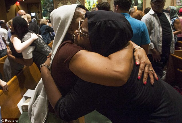 Embrace: Members of the New York congregation hug each other on Sunday after the news that Zimmerman would walk free