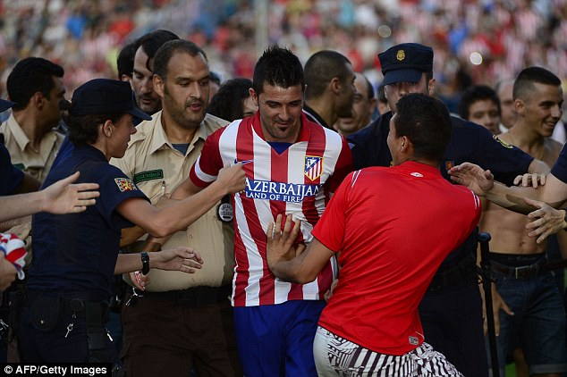 Mobbed: Fans invade the pitch in Madrid as David Villa is unveiled as their newest signing