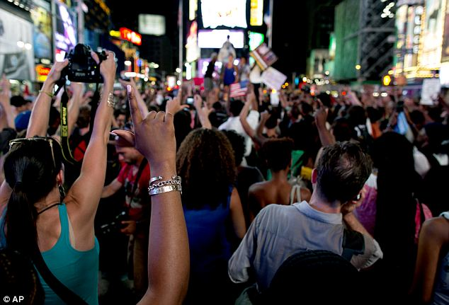 Calling for justice: Marchers hold up their hands in solidarity as they gather on Times Square Sunday