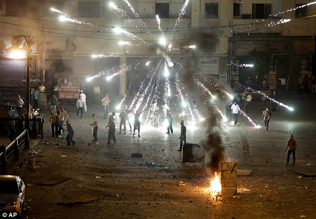 Ongoing clashes: A firework fired by opponents of ousted President Mohammed Morsi explodes over his supporters during clashes in downtown Cairo last night