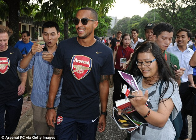 Mobbed: Arsenal forward Theo Walcott is greeted by fans in Vietnam