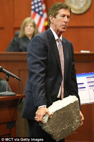 Hard hitting: By contrast, defense attorney Mark O'Mara held up a piece of the concrete sidewalk that he argued Martin used to bash Zimmerman's head