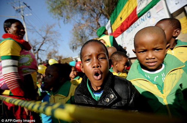 Celebration: These schoolchildren sing outside the hospital where Mandela is being treated for a lung infection
