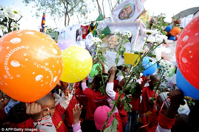 Thrilled: Thousands of South Africans today took part in charitable initiatives in a global outpouring of support on U.N.-designated 'Nelson Mandela Day'. Schoolchildren hold balloons and flowers outside his hospital