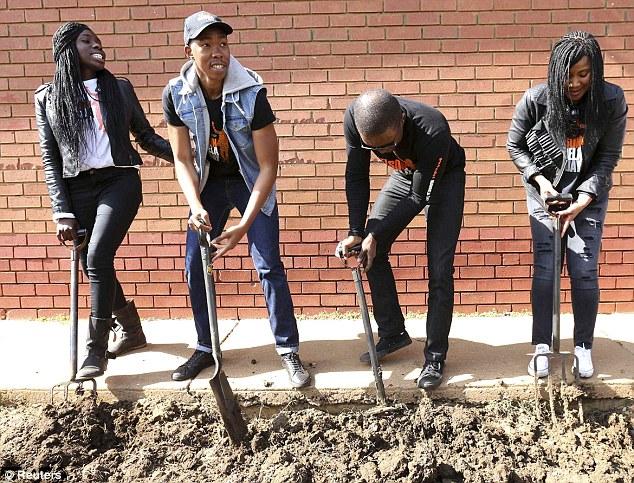 Working: Mandela's grandchildren, left to right, Adjoa Amuah, Mbuso, Zondwa and Tukwini work on a garden as they celebrate U.N.-designated 'Nelson Mandela Day'