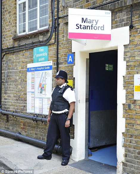 A police officer guards the rear entrance to the hospital