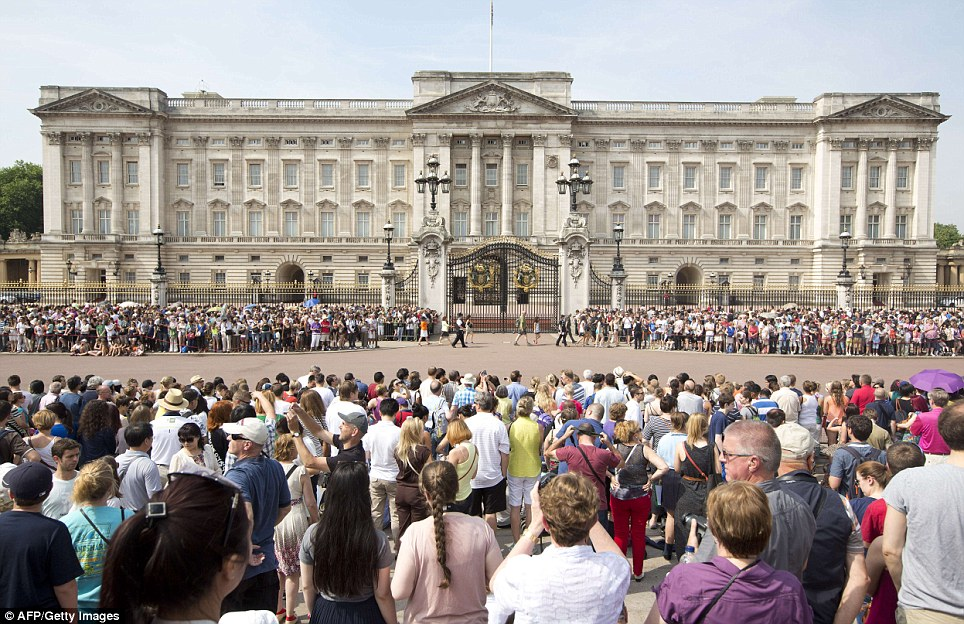 Vast: Crowds of tourists and well-wishers gather on the steps of the Queen Victoria Memorial Statue and at the gates outside Buckingham Palace today