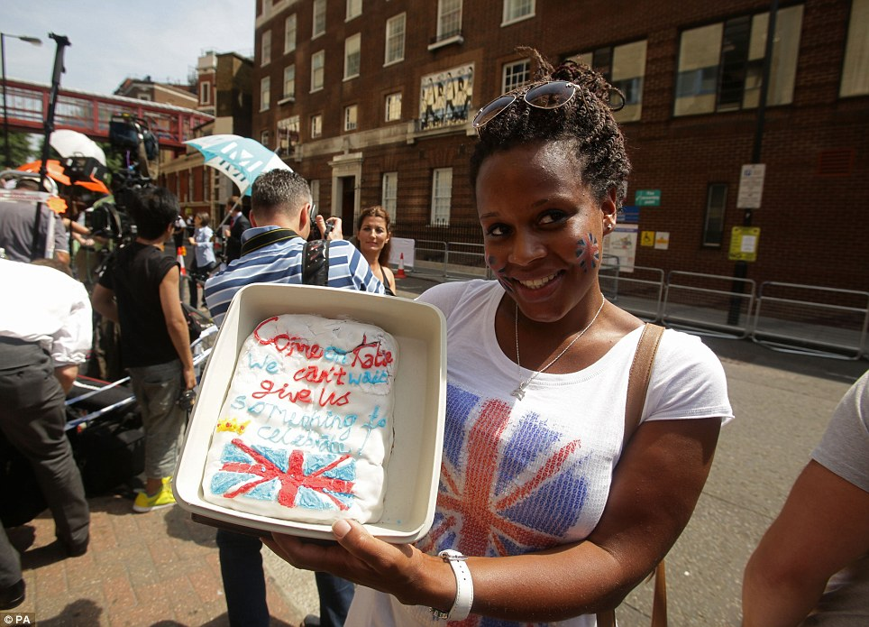 Baker: Teba Diatta holds a cake outside the Lindo Wing, which says 'Come on Kate, we can't wait, give us something to celebrate'