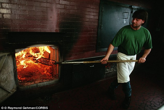 September 1996, North Carolina, USA --- Rick Byrd stokes the fire for the cooking pit in a barbecue restaurant in Lexington on a typical Saturday, workers will cook 95 pork shoulders each weighing 16 lb
