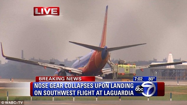 The disabled plane is seen here with its tail jutting into the air and its nose planted on the tarmac