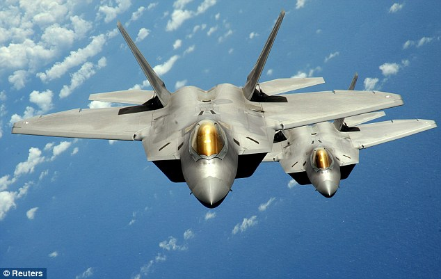 Fighter Pilot Shortfall: Two U.S. Air Force F-22 Raptor stealth jet fighters fly near Andersen Air Force Base