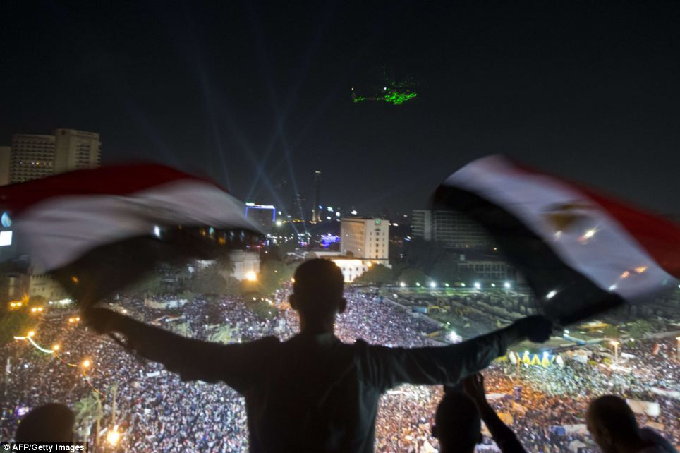 Support: A Egyptian man waves national flags as an army helicopter flies over supporters of the army in Tahrir Square