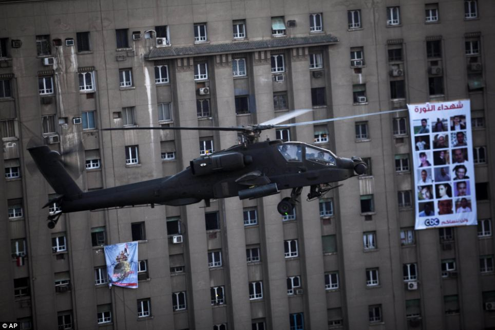 Security: A military helicopter patrols the skies above Tahrir Square where hundreds of thousands of supporters of the army gathered on Friday