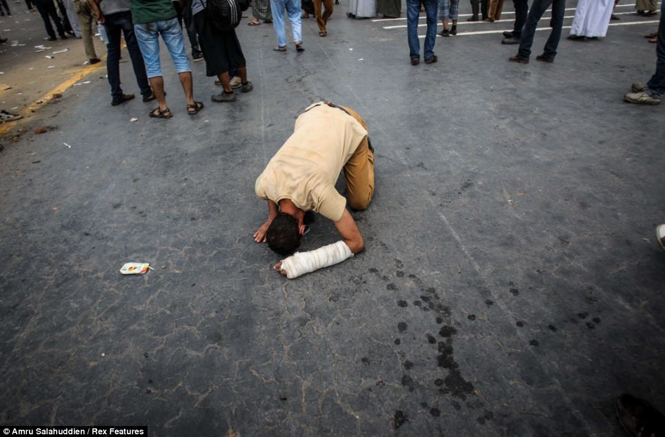 Distress: An injured supporter of Morsi kneels on the ground after clashes with riot police in the capital