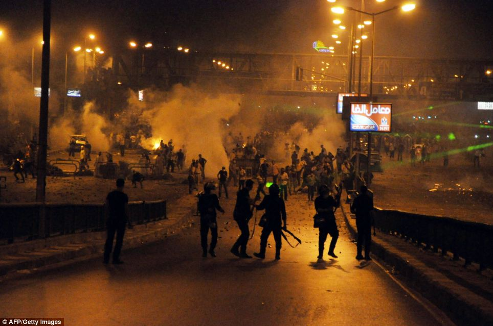 Conflict: Police stand back as teargas is fired into a crowd in Cairo in the early hours of Saturday morning