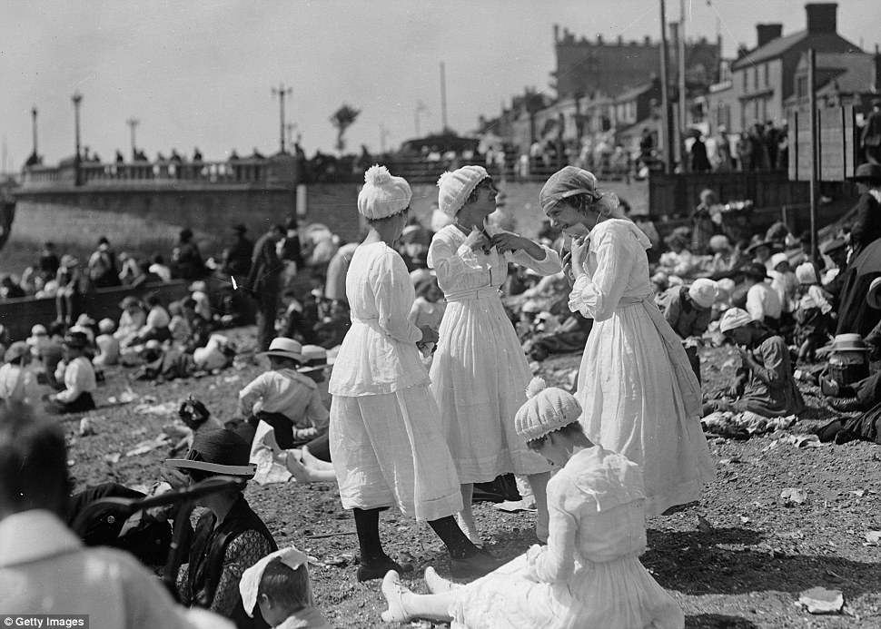 Bathing belles show off the modest white cotton calf length long sleeved dresses, complete with bathing caps adorned with bobbles, on the beach at Southend-on-Sea, Essex in August 1919