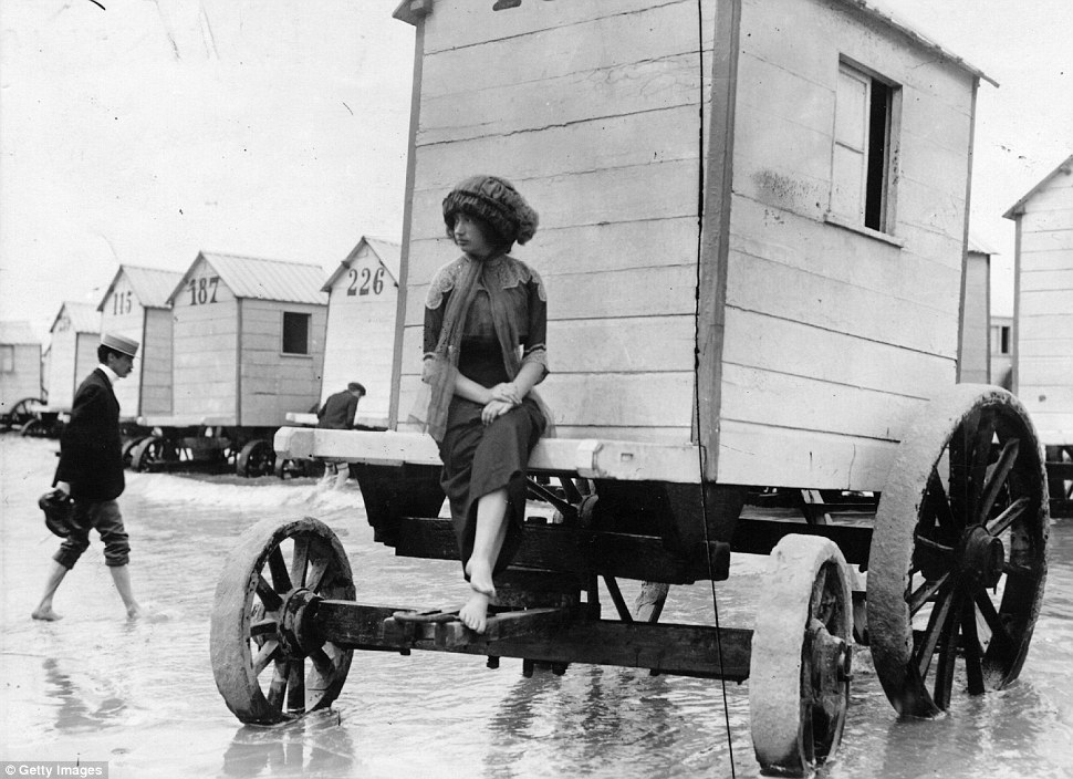 A woman perches on the edge of a bathing machine parked in shallow sea on Ostend beach in July 1911