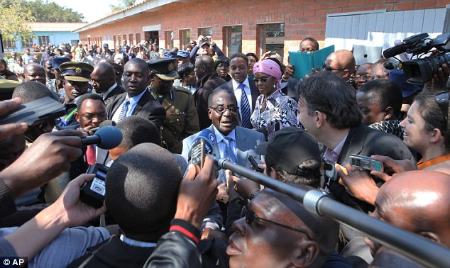 Scrum: Mugabe is surrounded by the press after casting his vote - he insists he will leave office if defeated