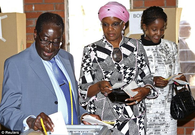 Vote: Robert Mugabe casting a a ballot in the election that will decide his fate, watched by his wife and daughter