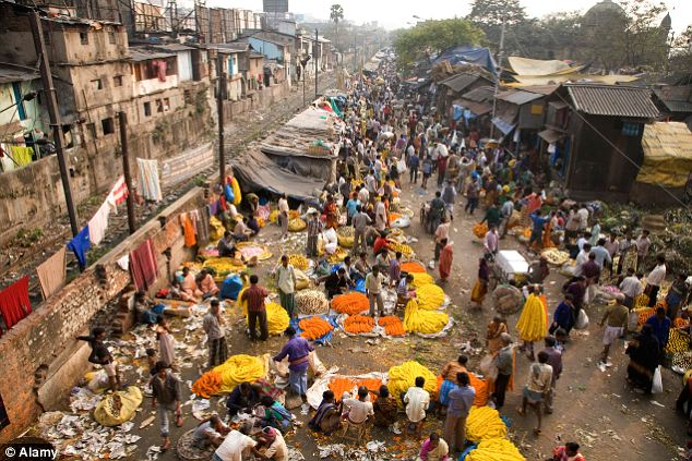 Densely populated: People buy and sell flowers at the colourful Mullick Ghat Flower Market in Howrah, near to where an 11-year-old girl was allegedly burned to death by men after she resisted their rape attempt