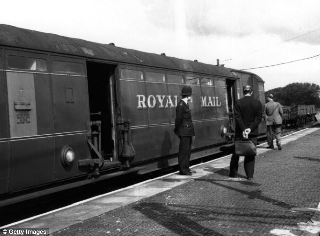 Looking for clues: Investigators are pictured examining the train after the robbery 50 years ago
