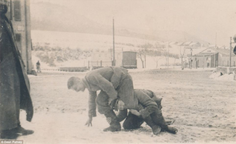 Pictured, two soldiers wrestle in the snow