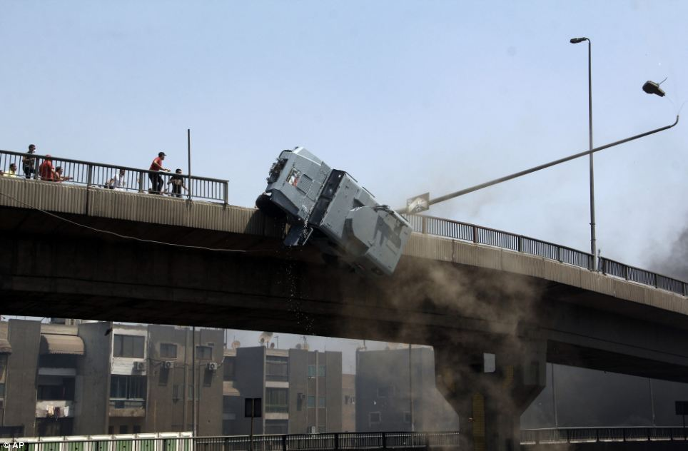 The police vehicle crashes through a fence as it is pushed off the 6th of October bridge in Cairo by protesters as violence in the capital escalated