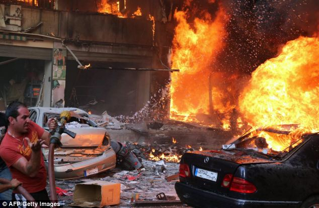 Lebanese emergency workers attempt to tackle the flames at the site of a car bomb in southern Beirut