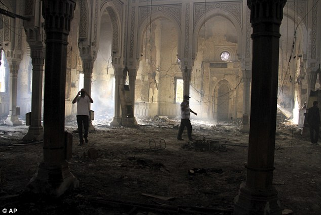 Eerie: Egyptians walk among the burned remains of the Rabaah al-Adawiya mosque, in the centre of the largest protest camp of supporters of ousted President Morsi, that was cleared by security forces