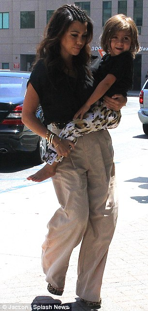 Keeping him close: Kourtney toted her barefoot boy as they arrived at the hospital earlier in the day