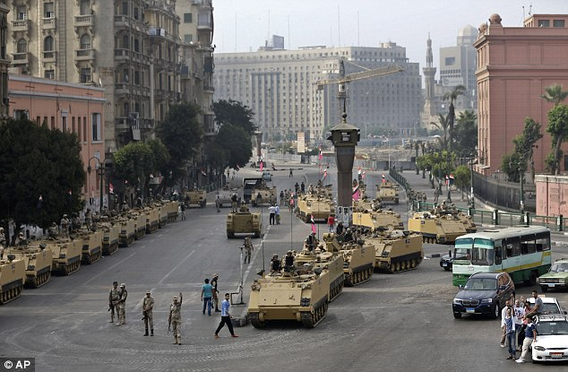 Fears: These armored vehicles guard an entrance to Tahrir square, in Cairo today as the country prepares for more bloodshed
