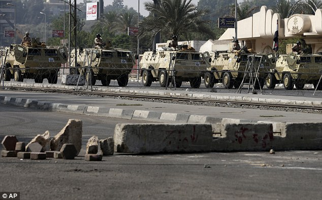 Edgy: Egyptian army soldiers take positions on top of their armored vehicles while guarding a street that leads to Rabaah al-Adawiya mosque