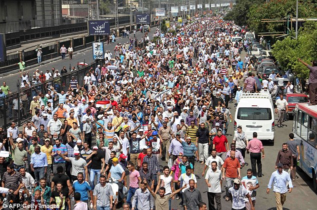 Fury: Egyptian Muslim Brotherhood supporters walk towards Ramses square in Cairo as they take part in a 'march of anger'. Violent clashes have already left 17 people dead