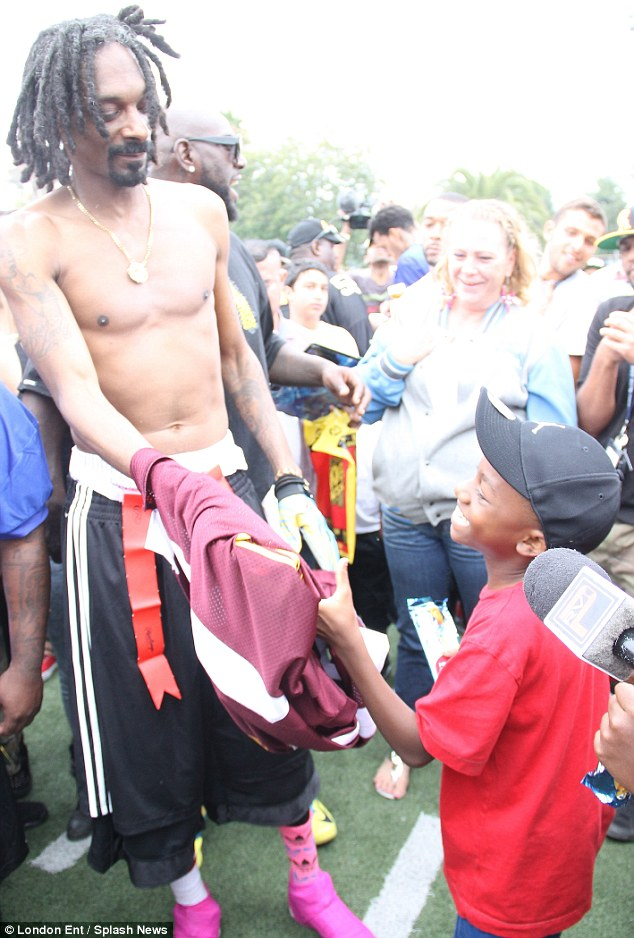 Lions share: Snoop could not resist giving a young fan his shirt at a charity football game in Los Angeles on Sunday
