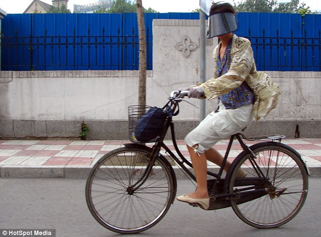 Fad: The benefits of protecting the skin appear to outweigh the risks of sun damage, plus crashing while cycling, for this Chinese fan of the new face-visor